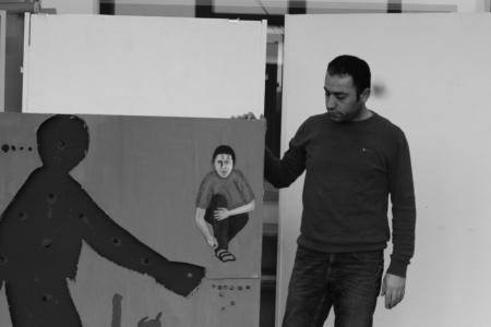 Das Foto zeigt Hüseyn Büyüktas, der sein Bild präsentiert: Ein grosser bemalter Karton, der die Geschichte von Ugur Kaymaz erzählt