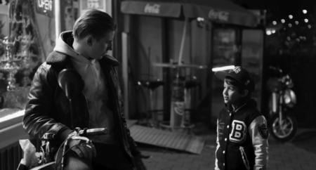 """Filmstill aus dem Film """"The Kids Are Alright"""" zeigt einen jungen Mann mit Motorrad, der mit einem kleinen Jungen spricht."""